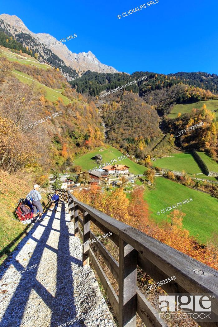 Stock Photo: People watch the landscape heated by autumn colors. Parcines Waterfall, Parcines, Val Venosta, Alto Adige/Sudtirol, Italy, Europe.