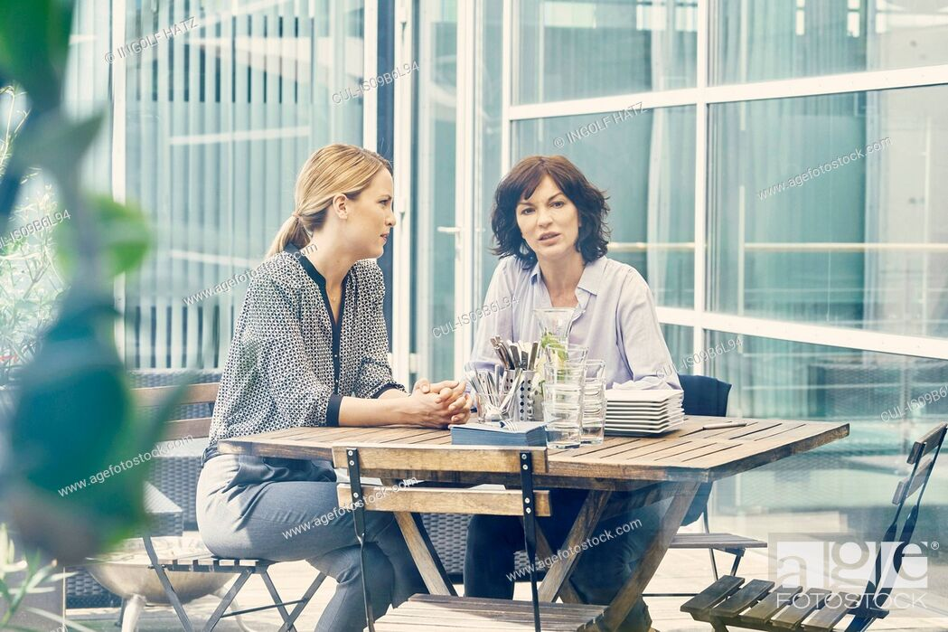 Stock Photo: Two businesswomen having discussion during business lunch outside office.