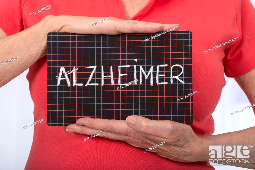 Stock Photo: Senior Woman 's hands holding a black slate with Alzheimer written on it.