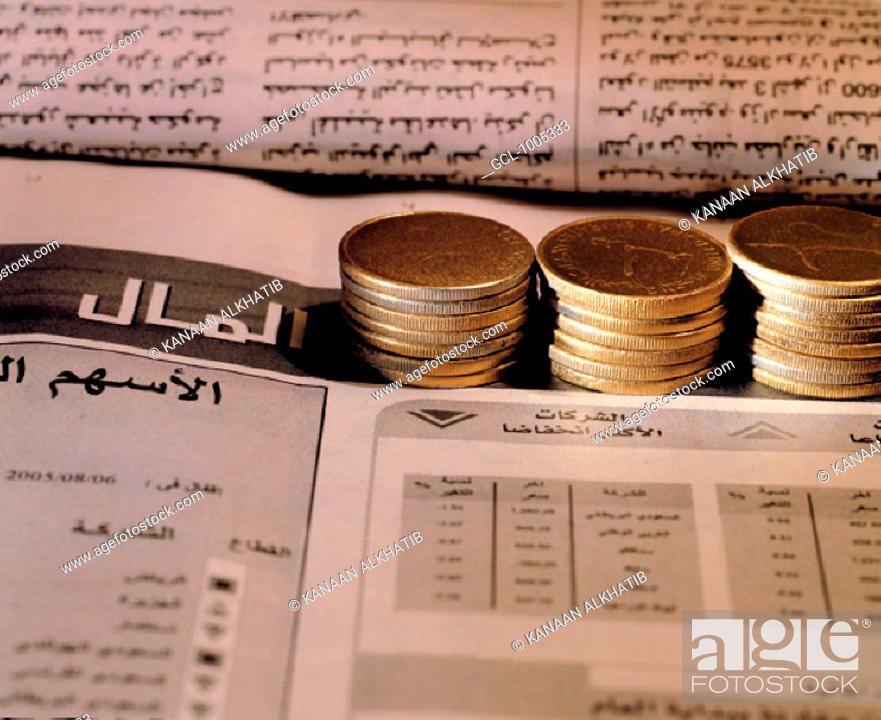Stock Photo: Piles of UAE coins on Arabic newspaper.