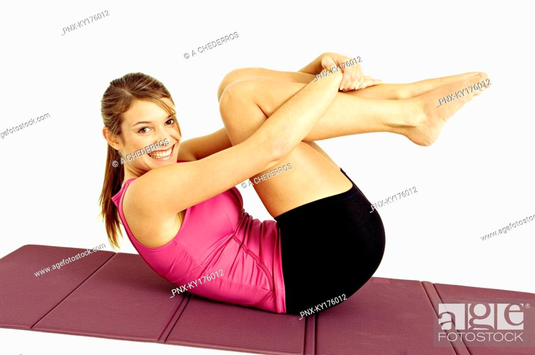 Stock Photo: Portrait of a young woman exercising on an exercise mat.