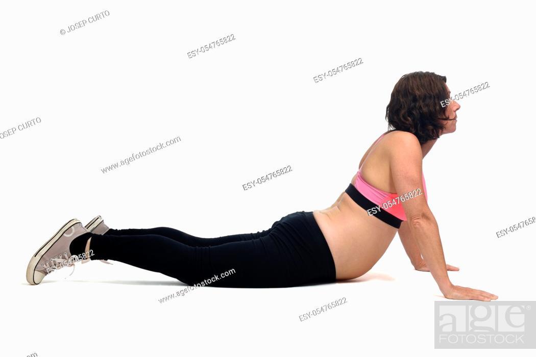 Stock Photo: pregnant woman doing floor exercises on white background.