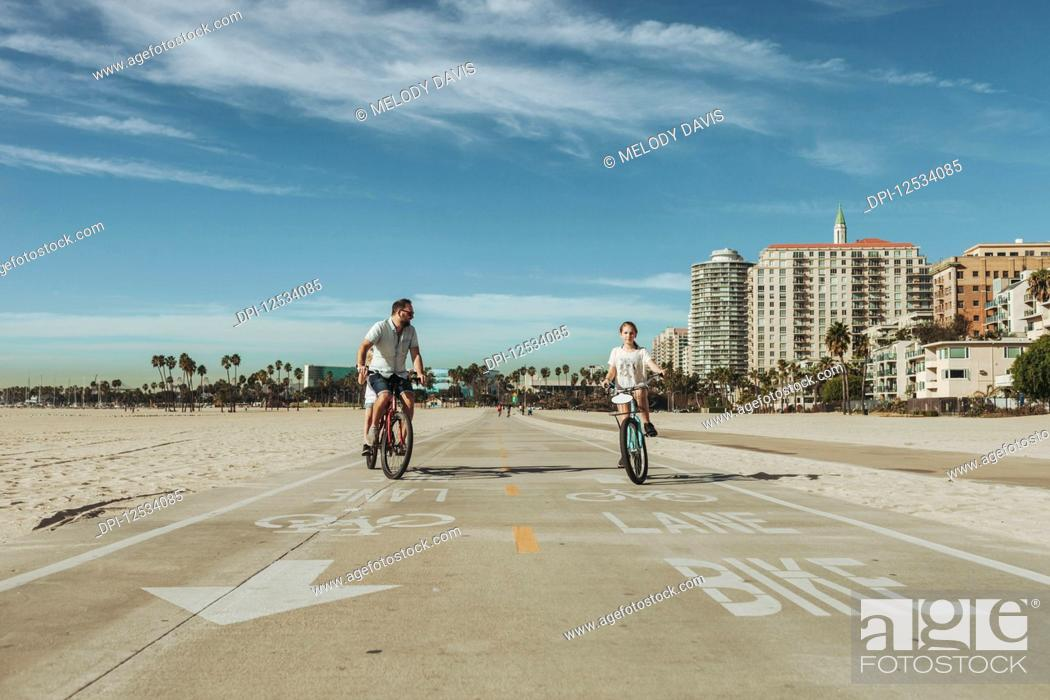 Imagen: A father and daughter riding bikes at Long Beach; Long Beach, California, United States of America.