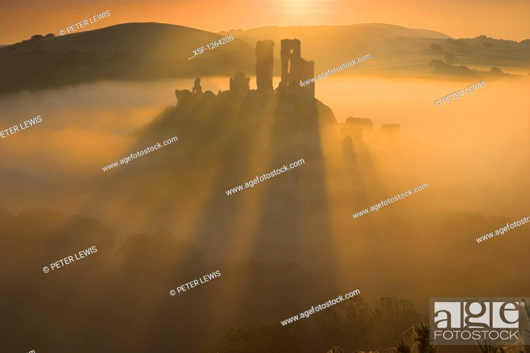 Stock Photo: Corfe Castle back lit by the sun causing long shadows to appear as it rises out of the mist at dawn Purbeck Dorset.