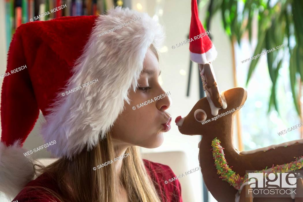 Stock Photo: Girl and gingerbread reindeer with Christmas caps.