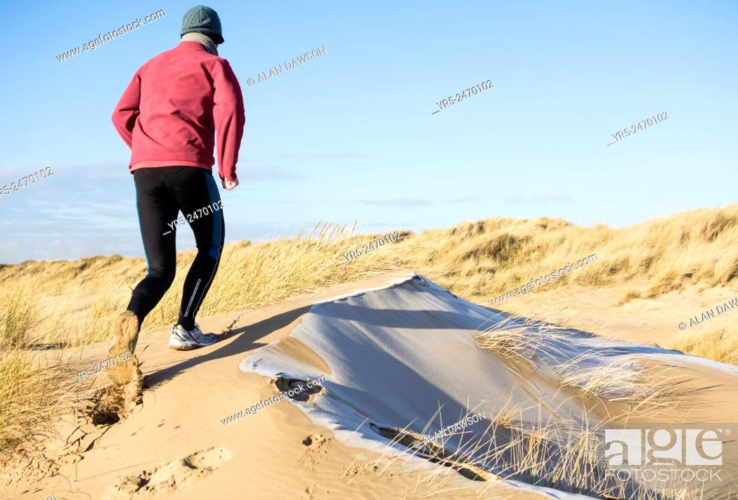 Stock Photo: Man jogging on frost coverd dunes on Seaton Carew beach, north east England, United Kingdom.