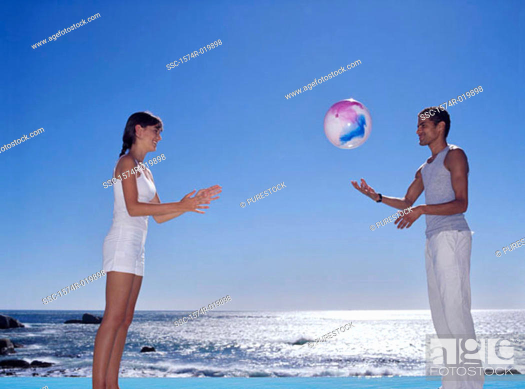 Stock Photo: Side profile of a young couple playing with a beach ball.