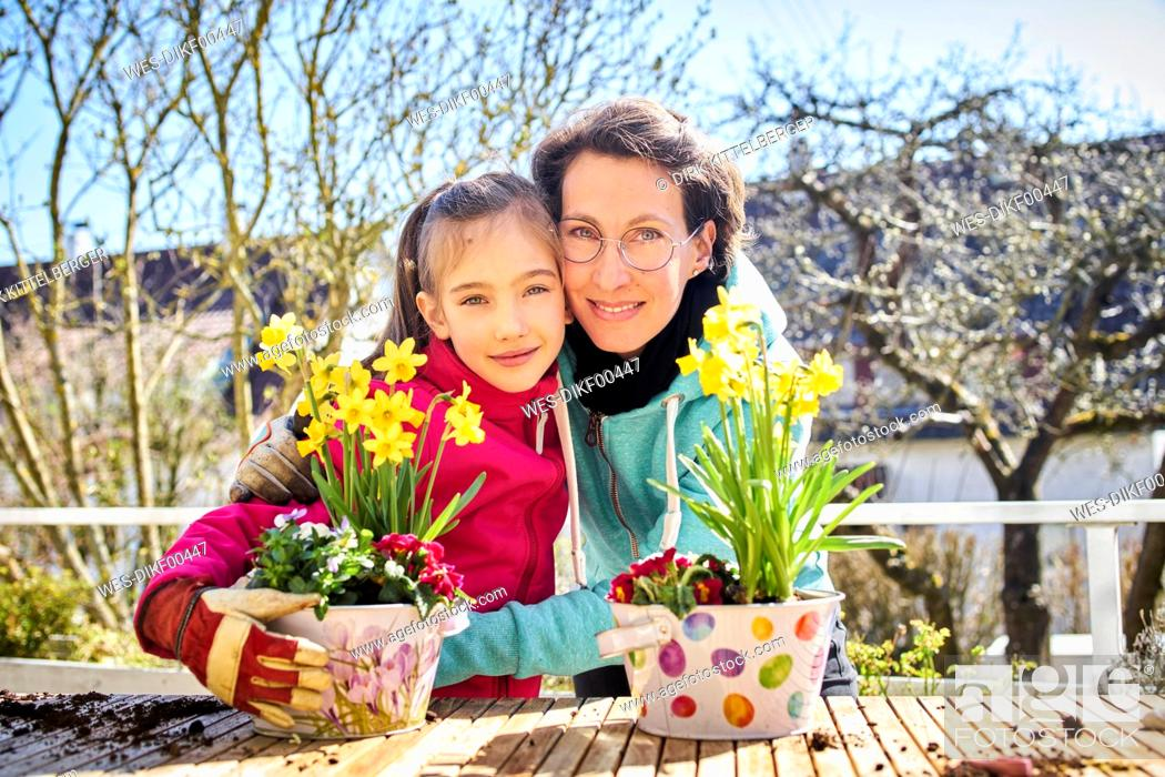 Stock Photo: Portrait of happy mother and daughter planting flowers together on balcony.