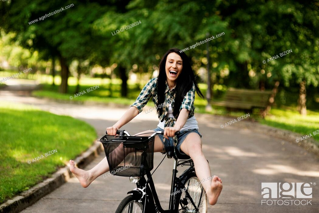 Stock Photo: Happy young woman cycling through the park, Debica, Poland.