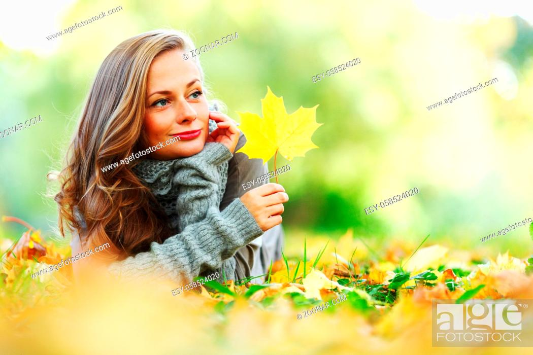Stock Photo: woman portrait in autumn leaf close up.