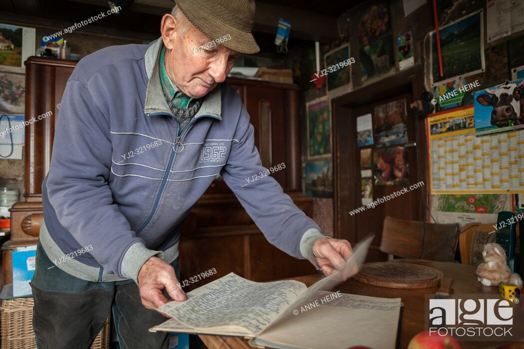 Stock Photo: Friendly elderly man in his kitchen showing his hand-written book with notes about the weather and important incidents. Germany.