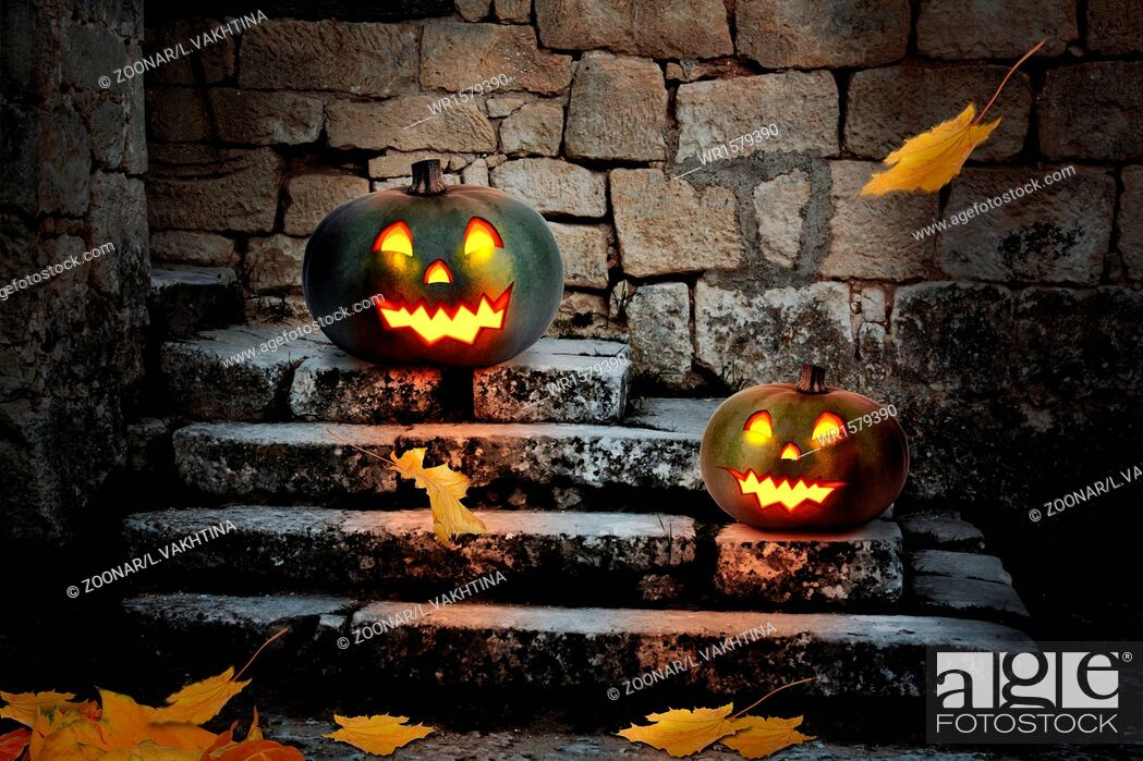 Stock Photo: Halloween pumpkins in the yard of an old house at night in the bright moonlight.