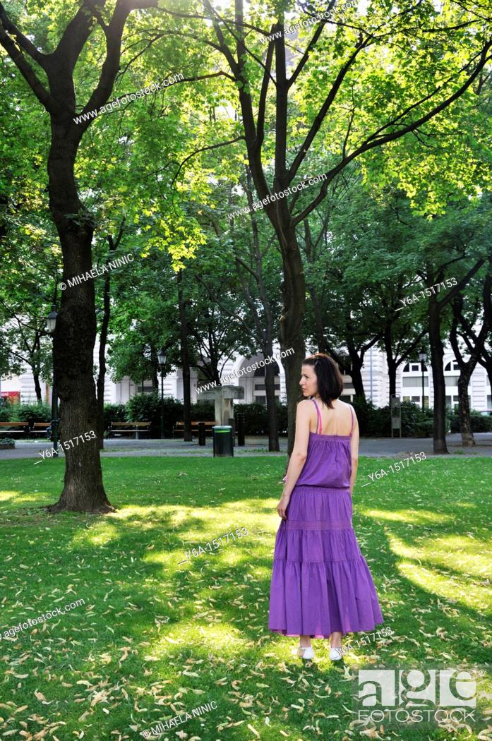 Stock Photo: Young woman wearing purple dress standing in a park outdoors.
