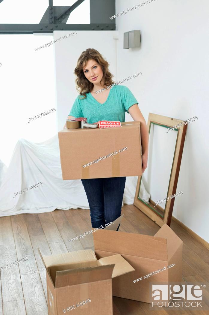 Stock Photo: Woman carrying cardboard boxes.