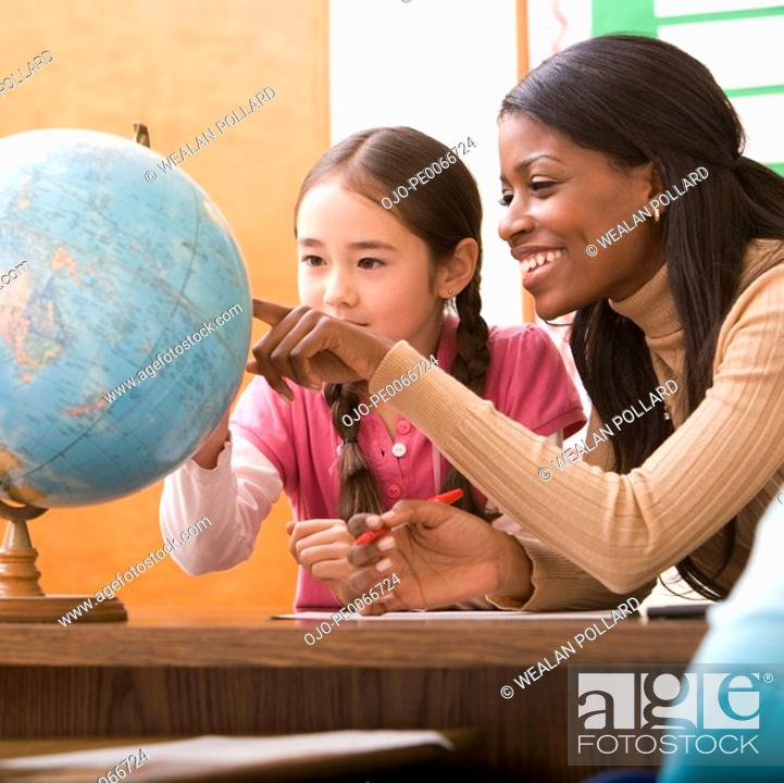 Stock Photo: Teacher and student looking at globe.
