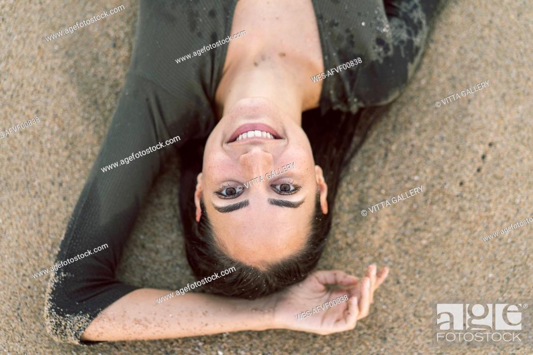 Stock Photo: Beautiful woman lying on the beach, portrait.