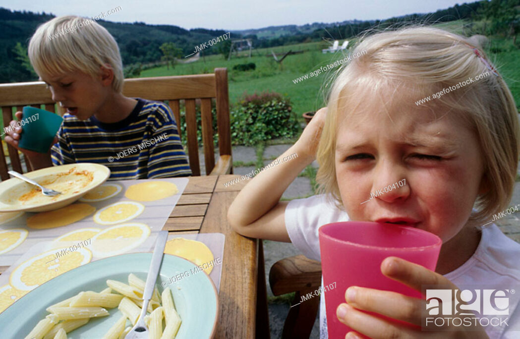 Stock Photo: A little girl and a boy, 1-5 years old, sitting in the garden, on the terrace, drinking juice and eating pasta.