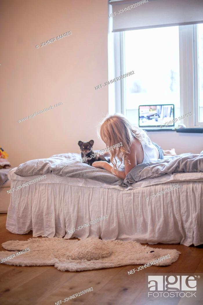Stock Photo: Girl with puppy lying down on bed.