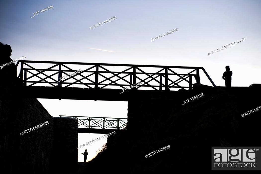 Stock Photo: Two seperate people standing, and footbridges, silhouetted at dusk, UK.