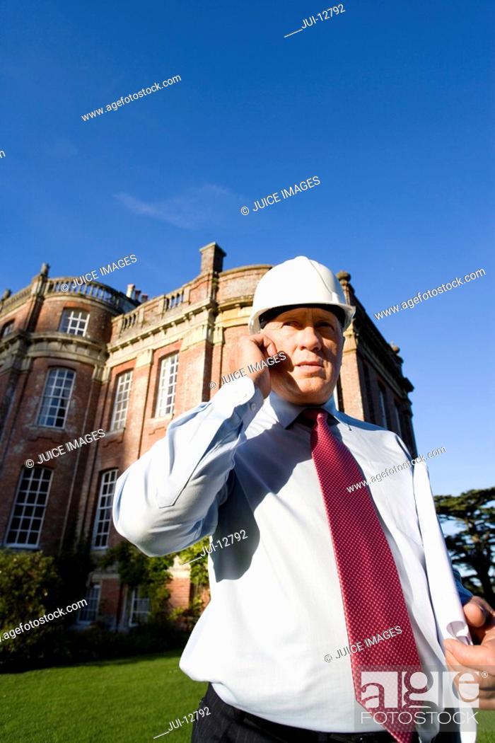 Stock Photo: Businessman in hardhat using mobile phone by manor house, low angle view.