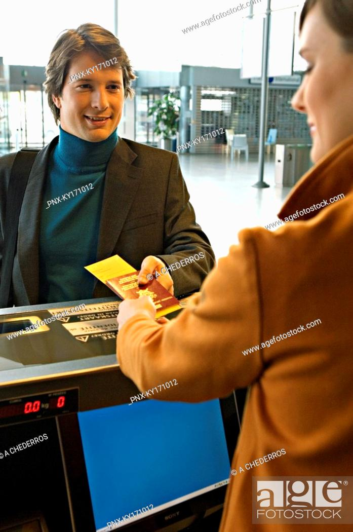 Stock Photo: Businessman with a female check-in attendant at an airport check-in counter.