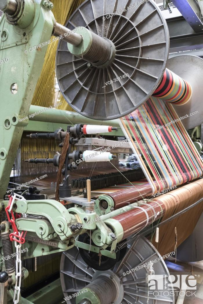 Stock Photo: Spoked industrial cylinders feeding brightly coloured yarns into a jacquard weaving loom, La Manufacture de Roubaix, France.