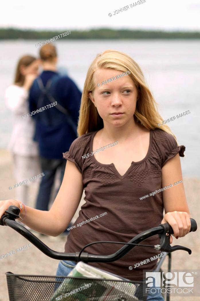 Stock Photo: Long Hair, Waist-Up, Color Image, Outdoors, Vertical, Caucasian Appearance, Leisure, Serious, Teenager, Blond, Bicycle, Bicyclist, Biker, Lifestyle, Alienation, Handlebar, Basket, Glance, T-Shirt, Suspicious, Casual Clothing, Girl, Cycle