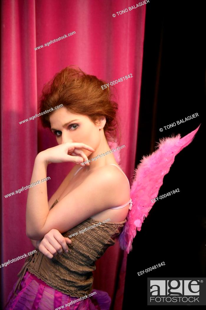 Stock Photo: Beautiful redhead woman with pink feather wings on romantic soft light.