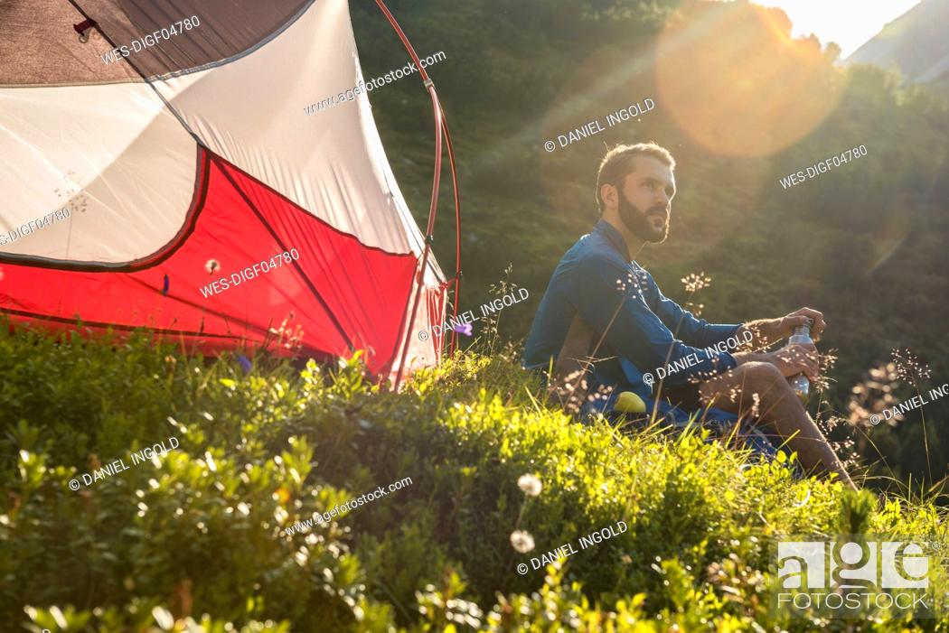 Photo de stock: Austria, Tyrol, Hiker taking a break, sitting in the grass by his tent.