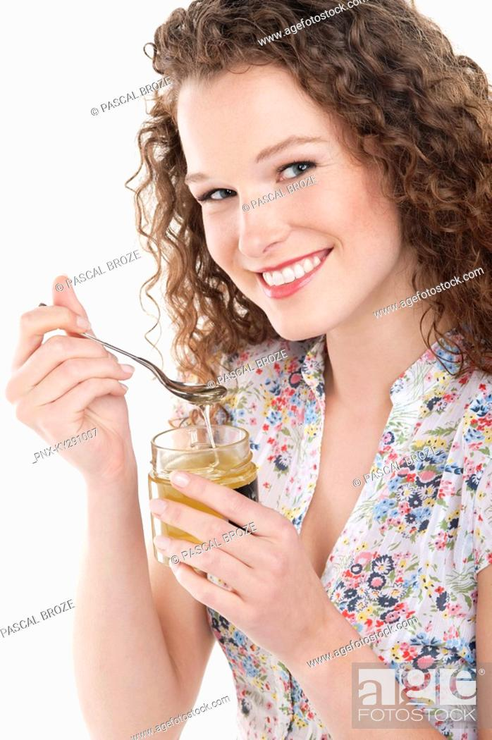 Stock Photo: Portrait of a woman eating honey.
