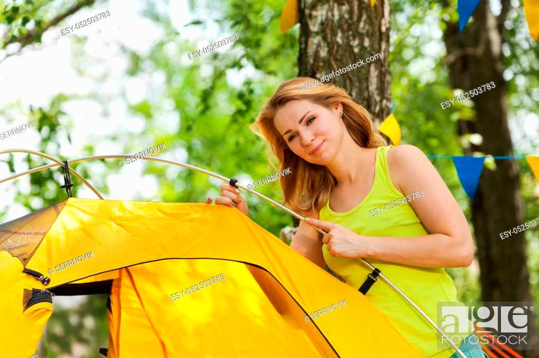 Stock Photo: Portrait of beautiful happy young woman putting up yellow tent in the woods in summer.