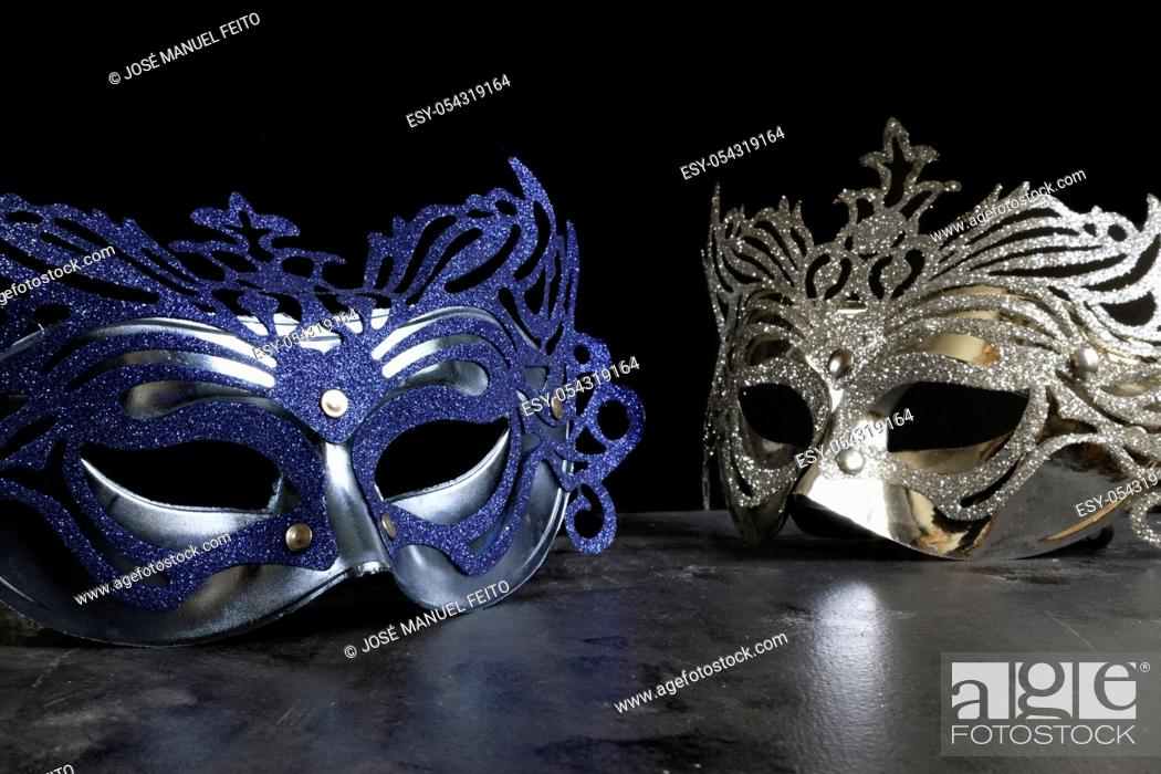 Stock Photo: blue and silvery carnival masks on dark and black background.