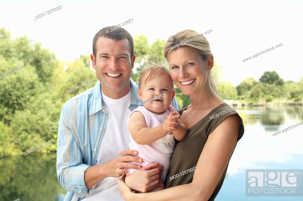Stock Photo: Couple with child standing by lake half length.