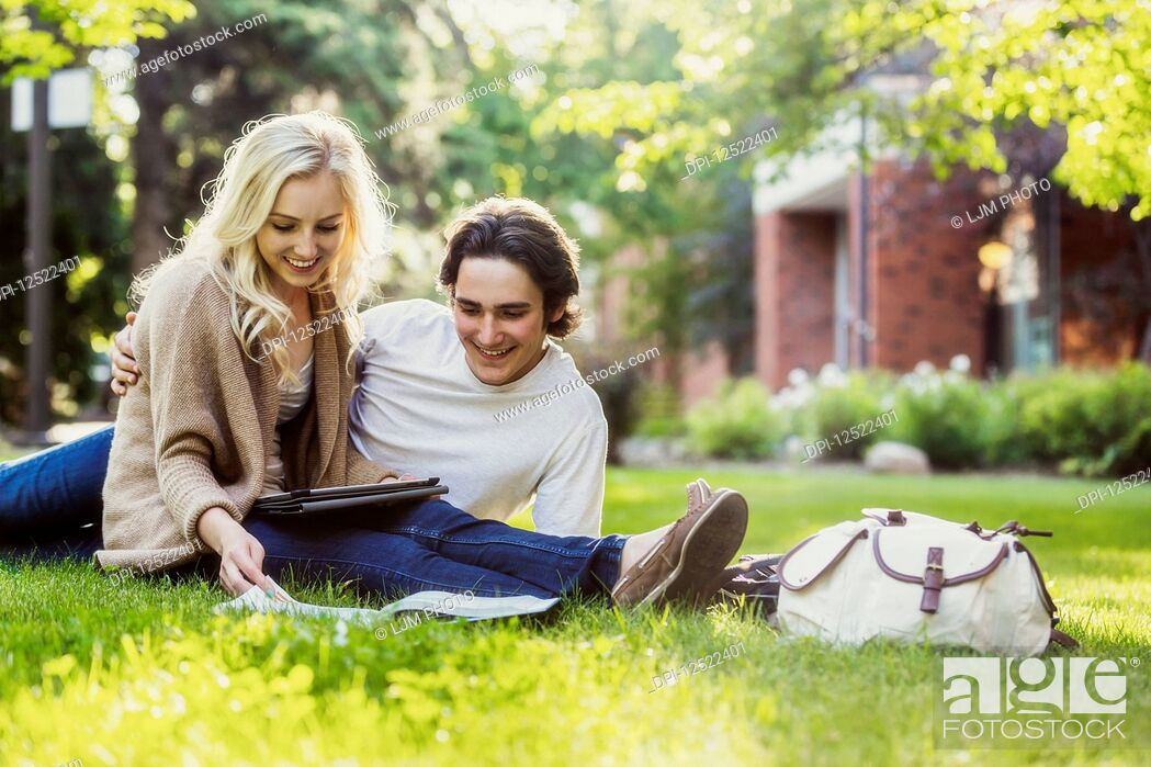 Stock Photo: A young couple studying outdoors on the grass on the university campus and looking through a textbook while using a tablet; Edmonton, Alberta, Canada.