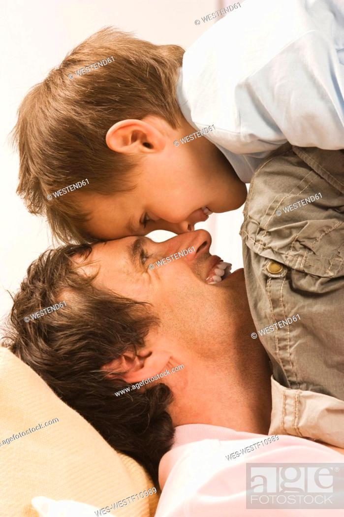 Stock Photo: Father and son 4-5, fooling about, head to head, close up.