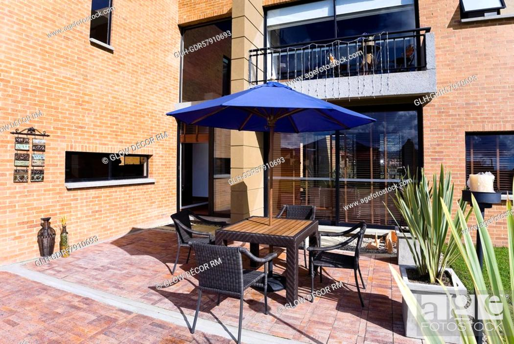 Photo de stock: Chairs with a patio umbrella in the courtyard of a house.