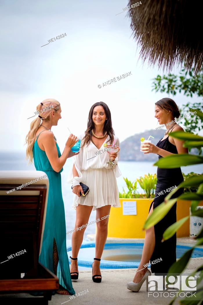 Stock Photo: Three young attractive women in elegant dresses at an outdoor cocktail party in Puerto Vallarta, Mexico.