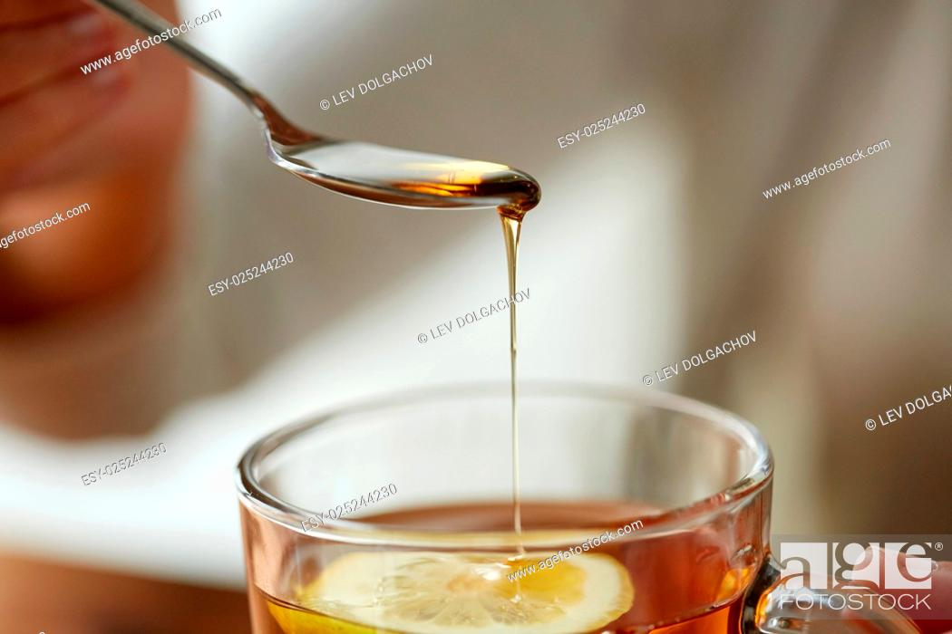 Stock Photo: healthy food, eating and ethnoscience concept - close up of woman adding honey to tea cup with lemon.
