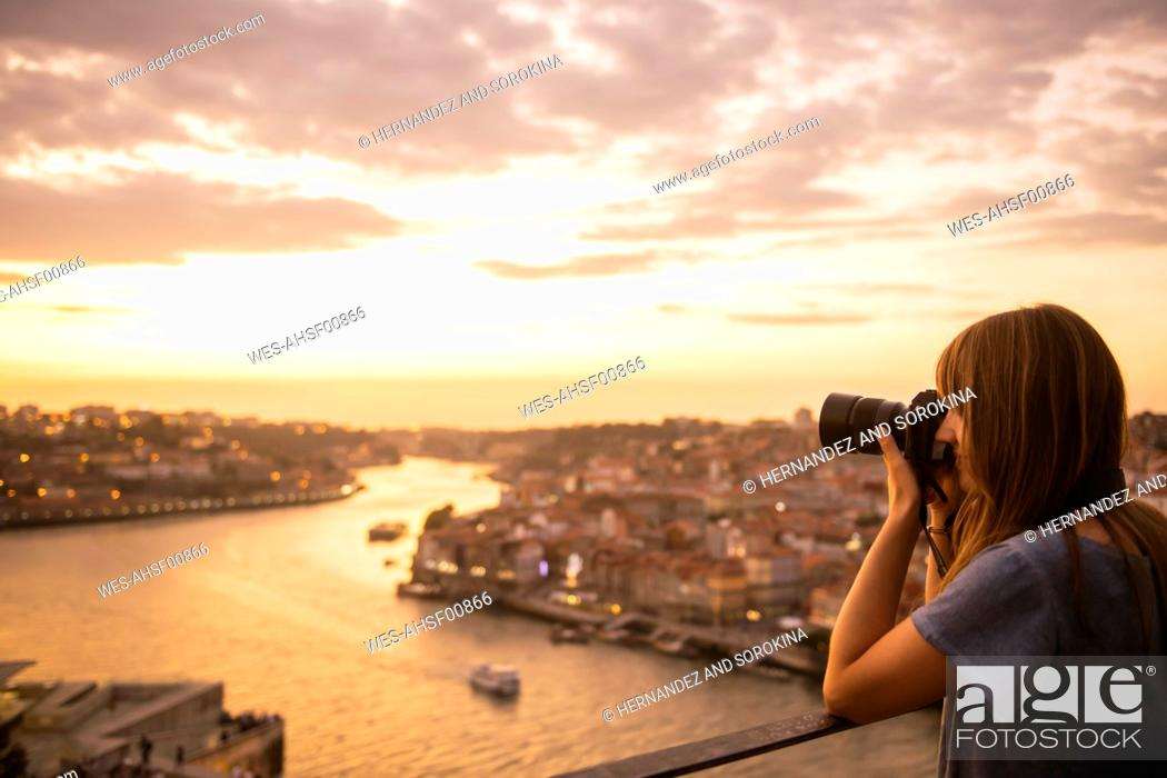 Stock Photo: Woman taking a photo of Porto at sunset, Portugal.