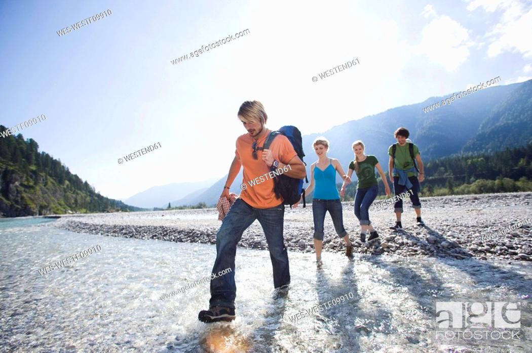 Stock Photo: Germany, Bavaria, Tölzer Land, Young friends walking through river.