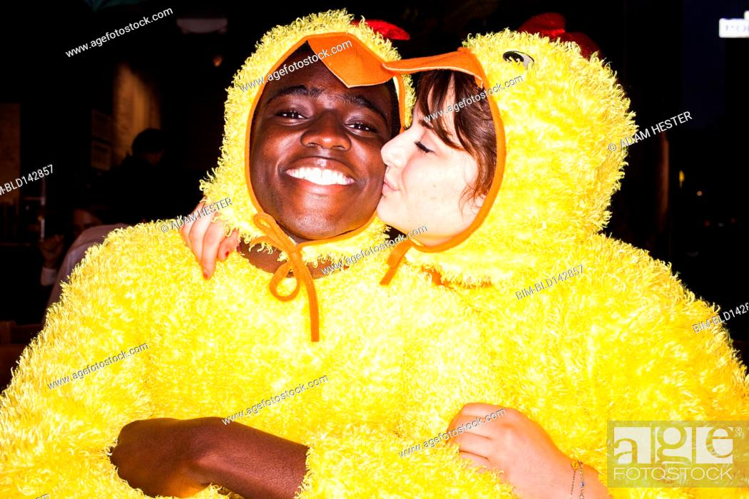 Stock Photo: Couple kissing in chicken costumes.