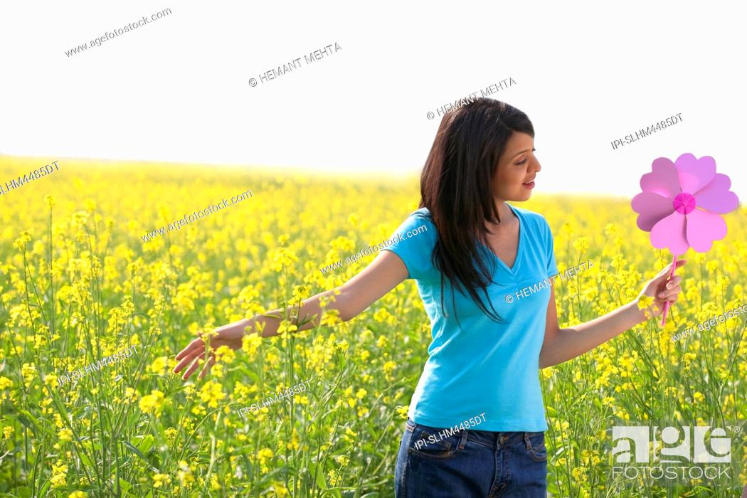 Stock Photo: Woman holding a pinwheel in a field.
