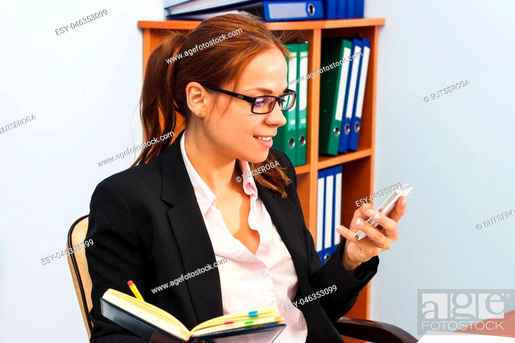 Stock Photo: Working situation in the office: Woman holds a phone and a datebook, soft focus background.