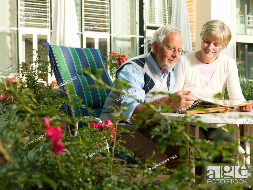 Stock Photo: Senior couple looking at a photo album.