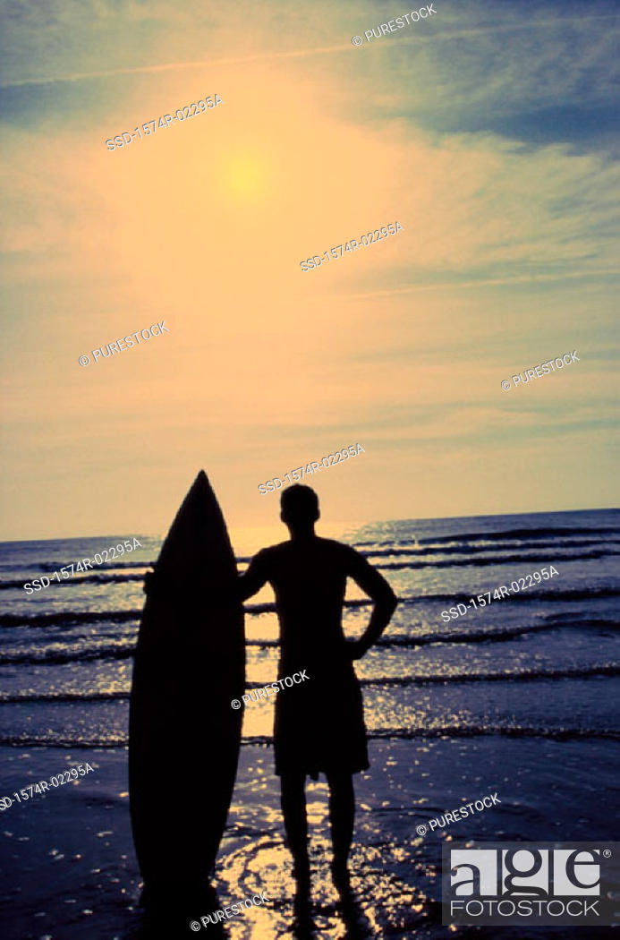 Stock Photo: Silhouette of a man holding a surfboard standing on the beach.