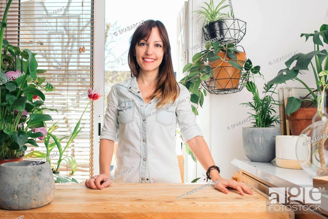 Stock Photo: Portrait of smiling woman with plants around her.