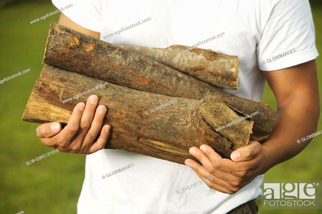 Stock Photo: Mid section view of a young man holding firewood.