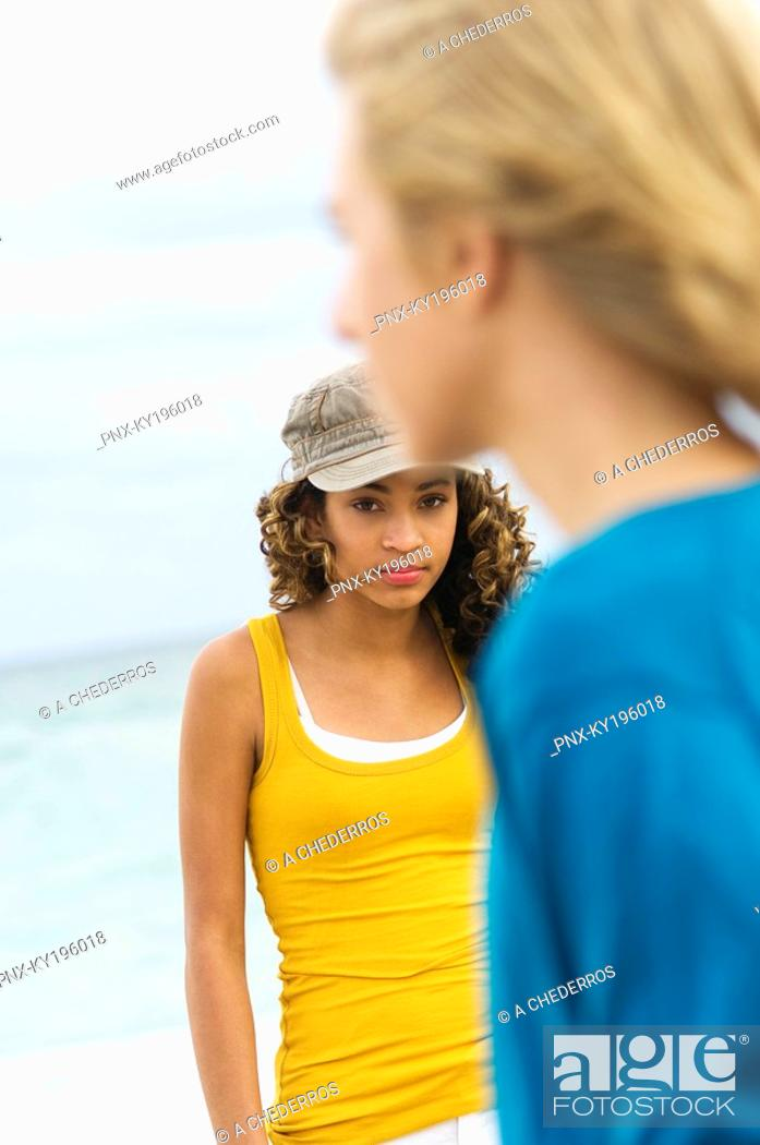 Stock Photo: Teenage boy standing with a girl on the beach.