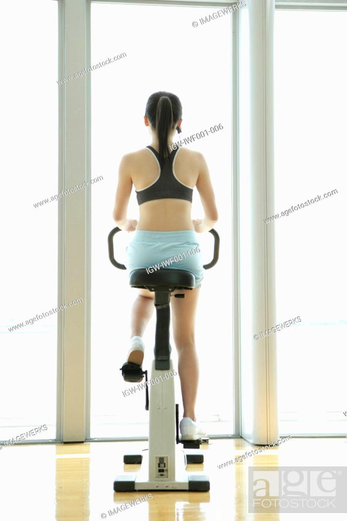 Stock Photo: Rear view of a young woman performing an exercise in a well equipped gym.