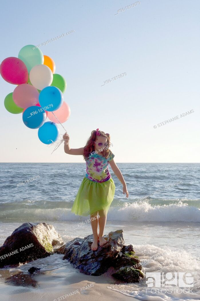 Stock Photo: young girl standing on rocks with balloons at the ocean.